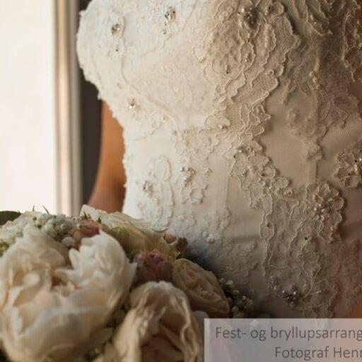 Brudekjole med blonde- og perledetaljer samt brudebuket med hvide blomster