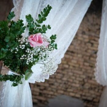 Blomsterbuket med grønne grene, lyserøde og hvide blomster bundet på vielsesportal