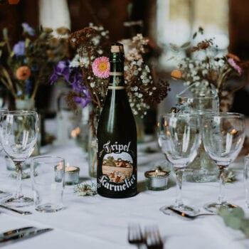 Centerpiece på bryllupsbord med grøftekantsblomster og rustikke øl