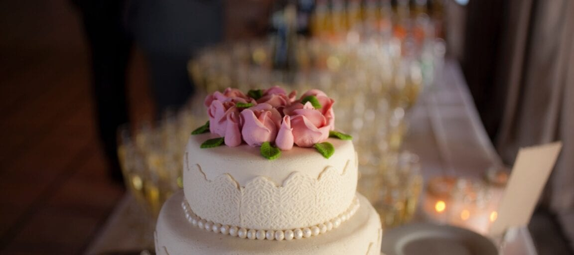 Hvid bryllupskage med roser på toppen til bryllup