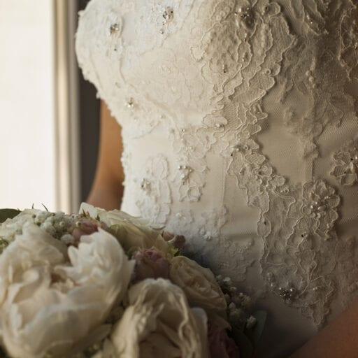 Detaljebillede af brudekjole med blonder og brudebuket med hvide og lyserøde blomster