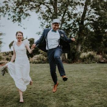 Hoppende brudepar med stort smil