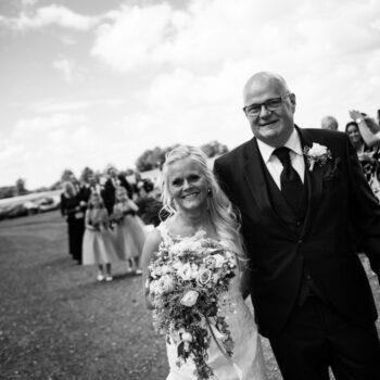 Smilende brudepar går sammen med brudebuket i hånden