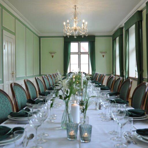 Den grønne stue i Hovedbygningen med grøn borddækning til fest