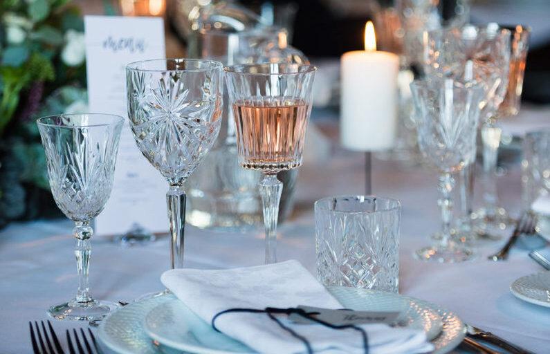 Detaljer fra bryllupsbord med service og fine krystalglas