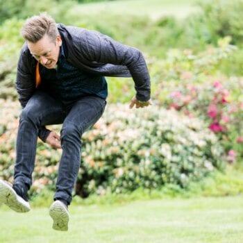 Mand hopper ved aktivitet i grønt parkområde