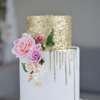 Bryllupskage med guldglimmer og lyse roser på siden