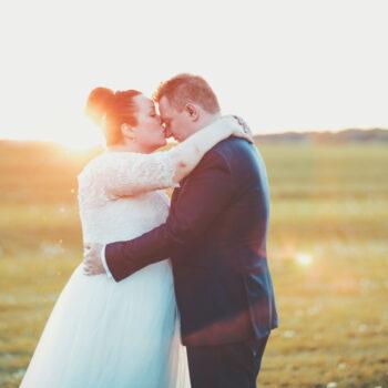 Brud kysser sin gom på næsen med solnedgangen i baggrunden