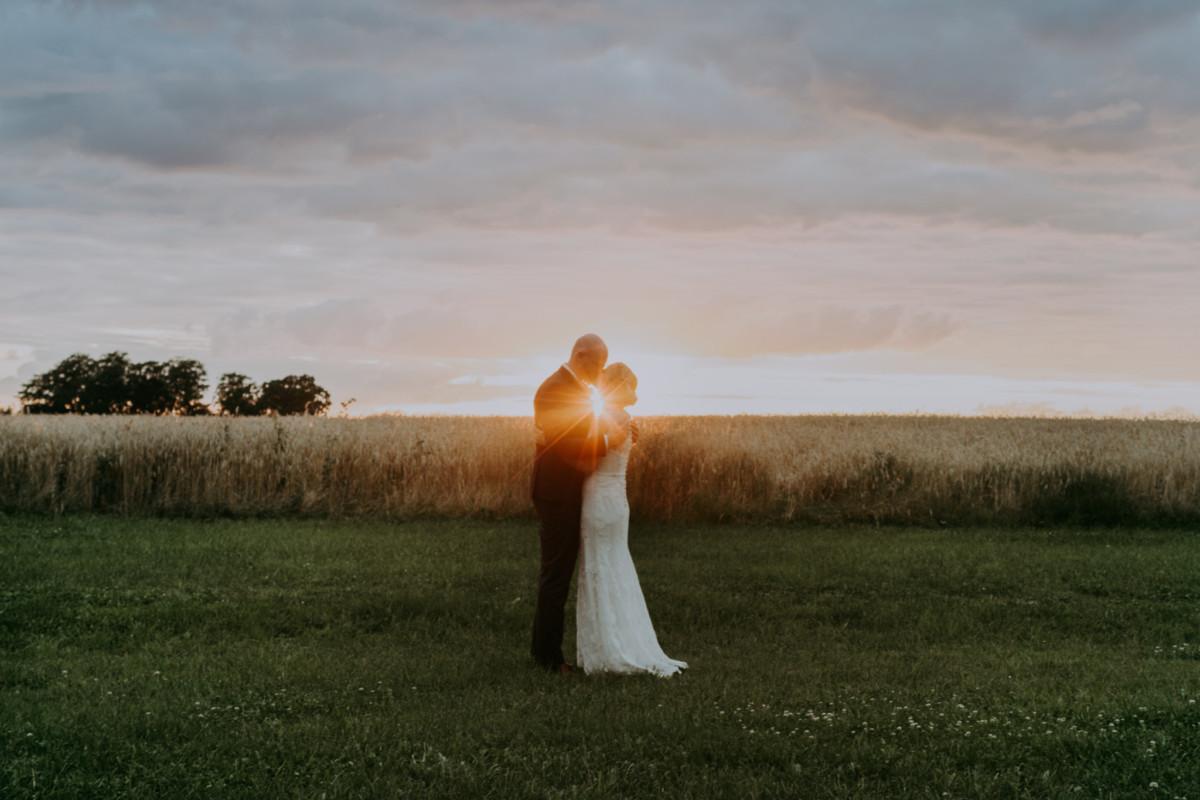 Bryllupsbilleder med solnedgang over markerne på godset