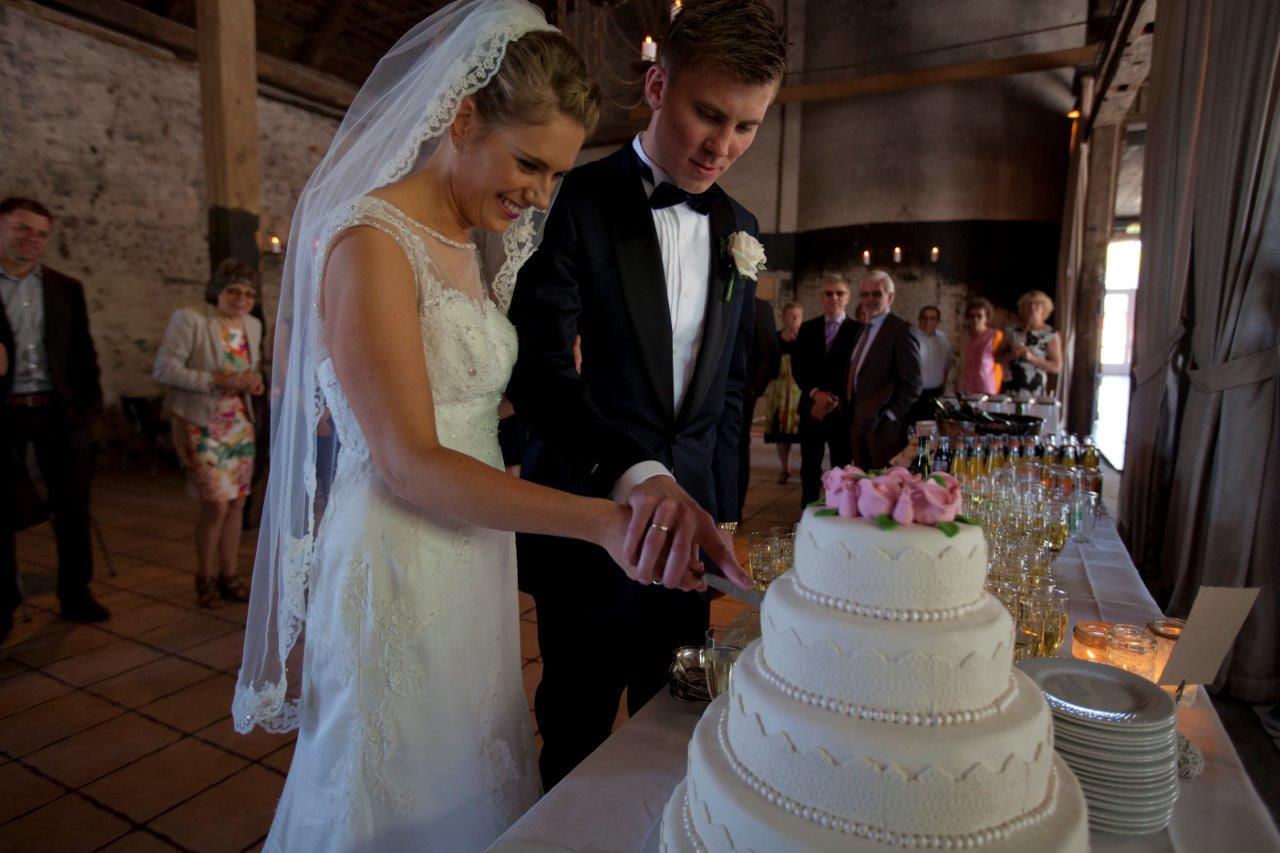 Brudepar skærer bryllupskage for