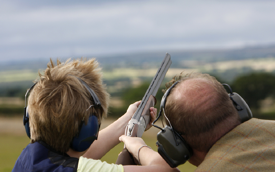 Ældre herre med dreng skyder lerduer