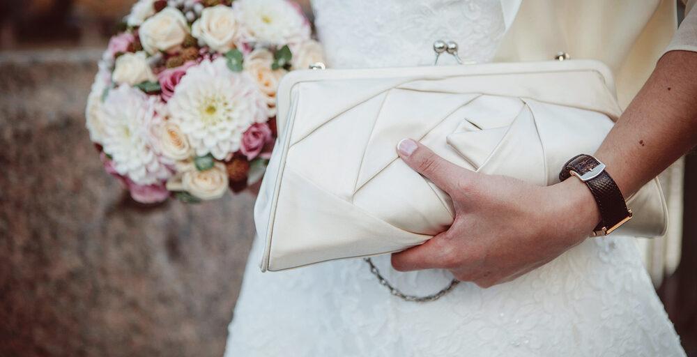 Brud med brudebuket og hvid håndtaske