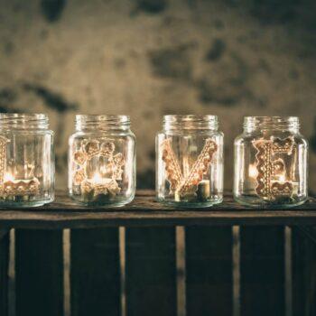 Tændte stearinlys i glas med bogstaver i stof på