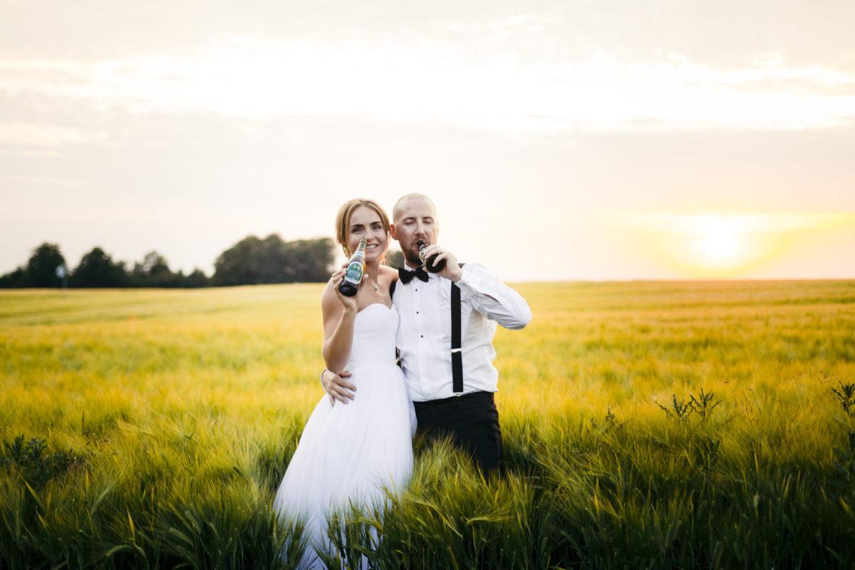 Brudepar med øl i solnedgang over markerne på godset