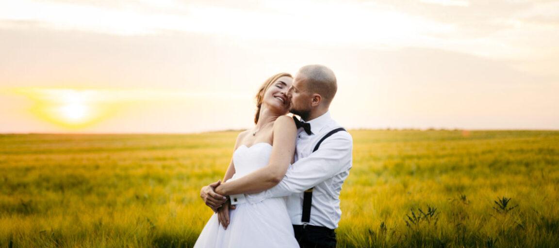 Bryllupsbillede af brudepar i mark med solnedgang
