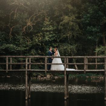 Brudepar på rustik bro i skov ved Sonnerupgaard Gods