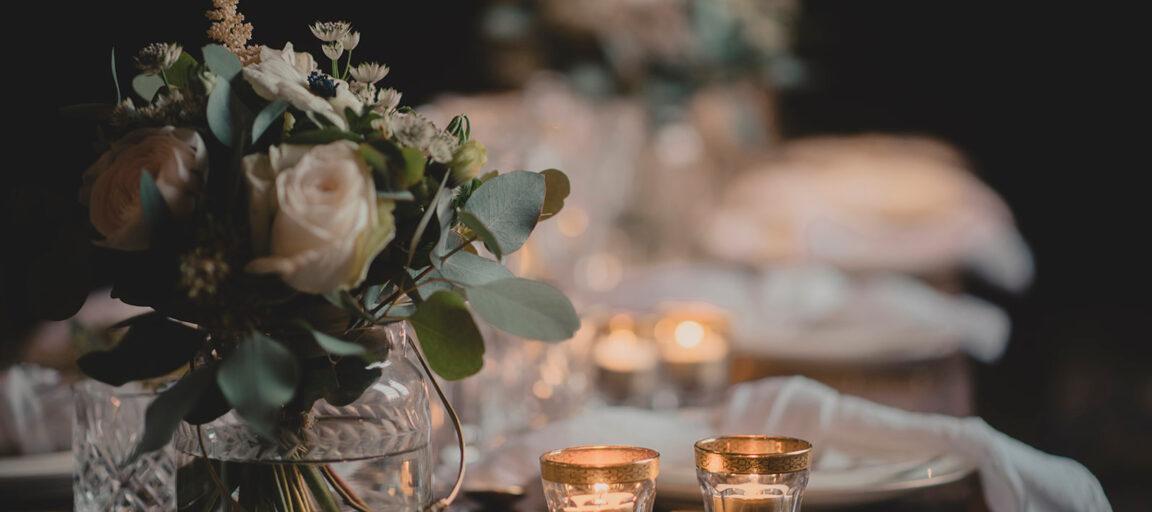 Borddækning bryllup med blomster, levende lys og hørservietter
