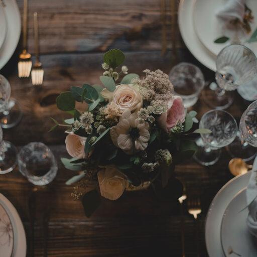 Borddækning med centerpiece af blomster og tallerkener med blomstermotiv