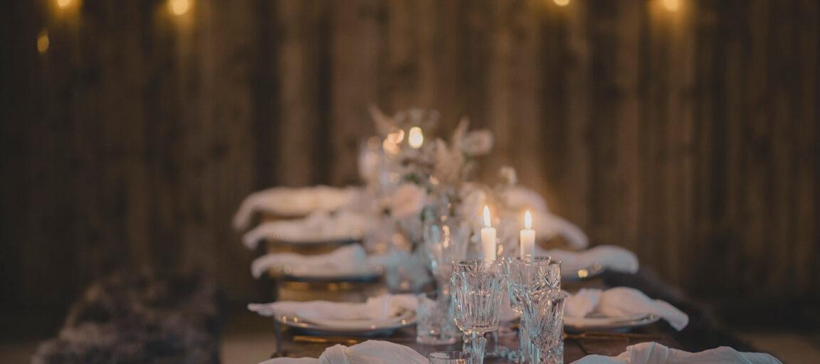 Plankebord til bryllup med hørservietter, krystalglas og levende lys i 1877-Laden på Sonnerupgaard