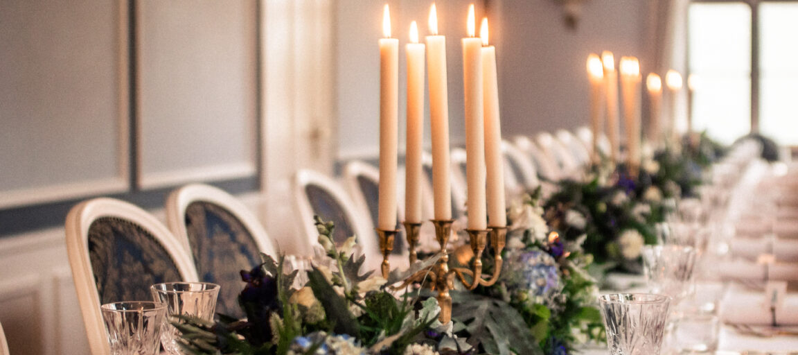 Borddækning til bryllup med blomster og levende lys samt lysekrone