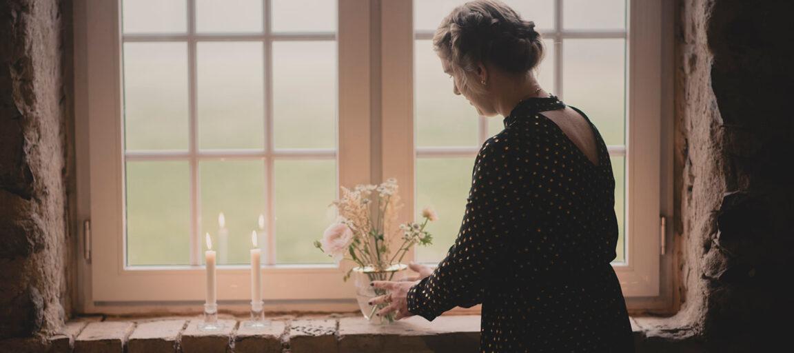 Maria Lyng bryllupsarrangør sætter blomster og levende lys i rustik vindueskarm i 1877-Laden