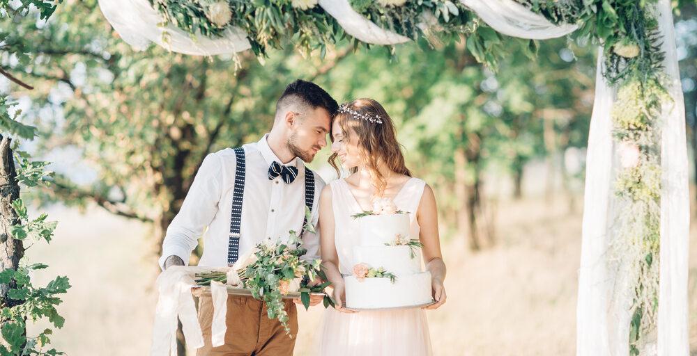 Brudepar med bryllupskage og blomster i hånden ved udendørsbryllup