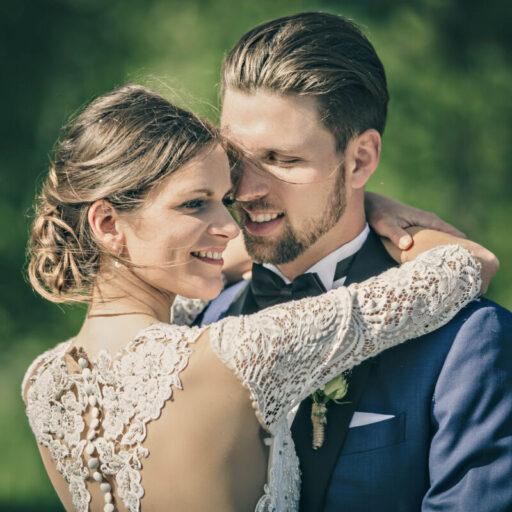 Brudepar smiler og holder om hinanden