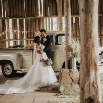 Brud og brudgom i rustik lade med flot truck