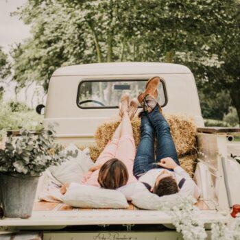 Brudepar slapper af på rustik truck med halmballer og blomster