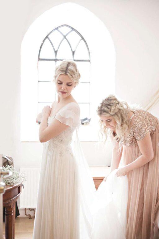 Brudepige hjælper brud i brudekjolen