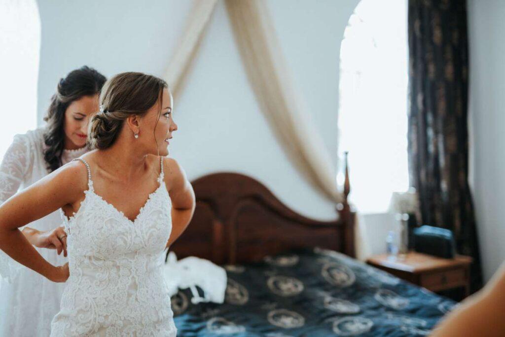 Brudepige hjælper brud i brudekjole med blonder