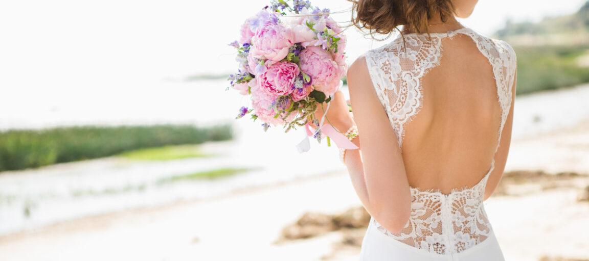 Brud med brudebuket iført brudekjole med åben ryg og blonder