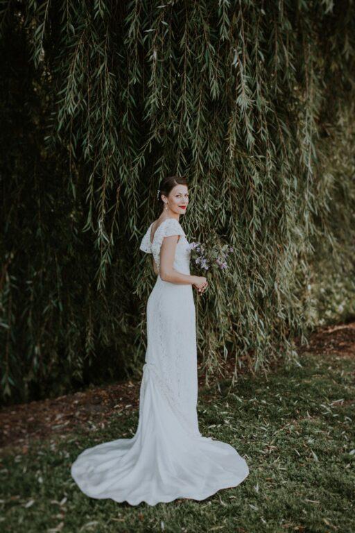 Brud står i lang brudekjole foran et piletræ