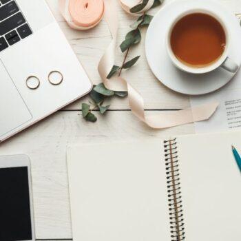 Computer, telefon, noter og kaffe på et bord