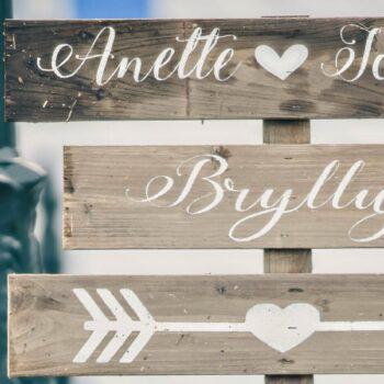 Vejviserskilt i træ til bryllup med navnene og pil på