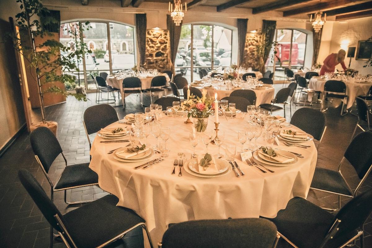 Bryllupsbord med levende lys og i gammel stald