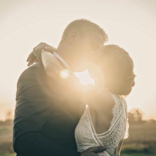 Kyssende brudepar i solnedgang