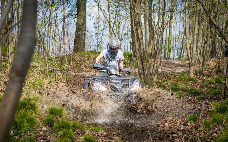 Teambuildinginstruktør kører ATV ned gennem mudder