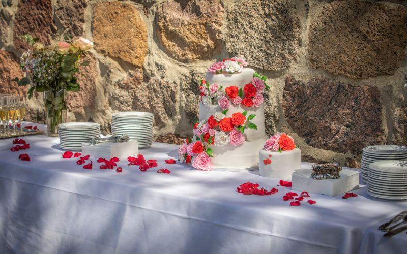 Hvid bryllupskage med lyserøde og røde roser på foran kampestensvæg
