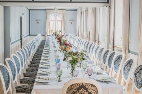 Bordopstilling og borddækning i Hovedbygningen til sommerbryllup med farverige glas og blomster