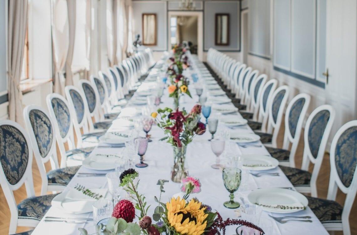 Langbord med farverige blomster og glas i Hovedbygningen