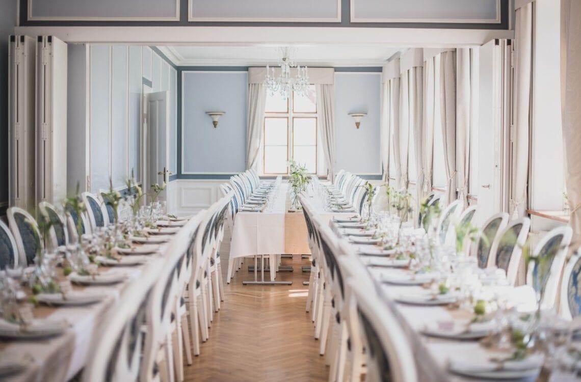 Langborde i Hovedbygningen med grønne blomster på bordene