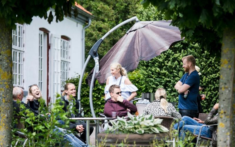 kollegaer hygger på terasse og drikker øl til en sommerfest
