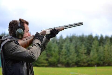 Mand sigter op i luften efter lerdue med geværet klar på skulderen set fra siden