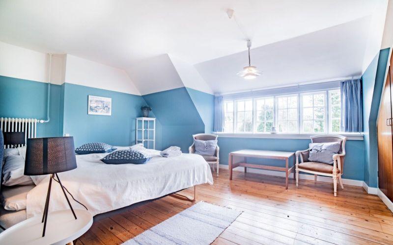 Blåt og hvidt hotelværelse med seng, stole og bord i Kavalerfløjen