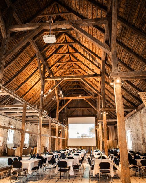 Konference opstilling med borde og stole i 1877-Laden med rustikke træbjælker