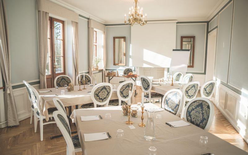 Møde og konference opstilling med borde, stole og projektor i Hovedbygningen