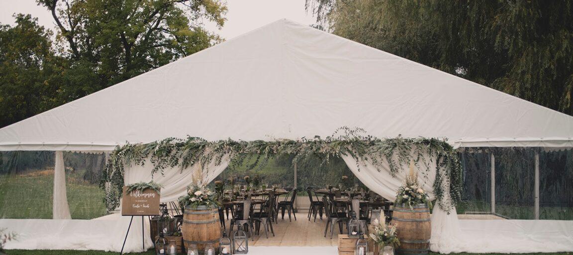 Hvidt telt klar til bryllup med rustikke borde og grønne grene langs indgangen