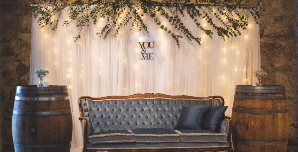 Selfiestation og fotovæg af tyl og lyskæder bag herskabelig sofa i blå