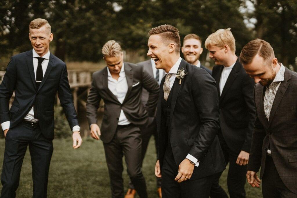 Gæster og gommen til bryllup iklædt jakkesæt